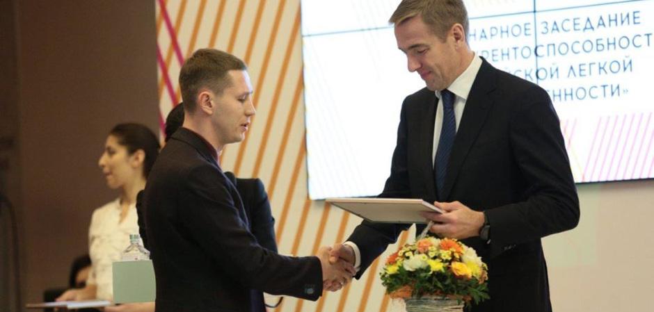 Виктор Евтухов, Минпромторг, вручает награду дизайнеру Дмитрию Шишкину