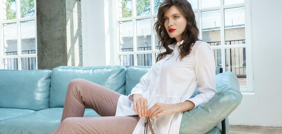 Девушка в одежде YARMINA сидит на диване